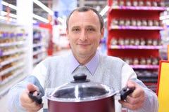 Elderly man in shop with pan in hands. Elderly smiling man in shop with pan in hands royalty free stock photo