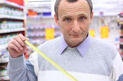 Elderly man in shop with  roulette in hands Stock Photos