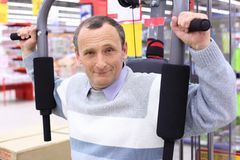 Elderly man in shop on sports exerciser Stock Images