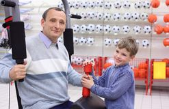 Elderly man in shop on  sports exerciser and boy Stock Photos