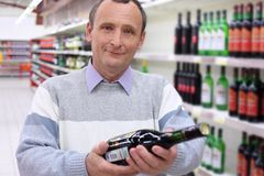 Elderly man in shop with wine bottle Royalty Free Stock Photos