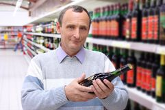 Elderly man in shop with wine bottle Stock Photography