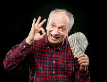 Elderly man showing fan of money Royalty Free Stock Photos