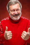 Elderly man showing ok sigh on a red background. Elderly man a red sweater showing ok sigh on a red  background Royalty Free Stock Photos