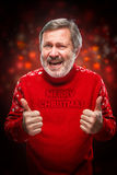 Elderly man showing ok sigh on a red background. Elderly man in a red sweater showing ok sigh on a red background. Christmas, holidays, gesture and people Stock Photography
