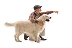 Elderly man showing something to his dog. On white background Royalty Free Stock Images