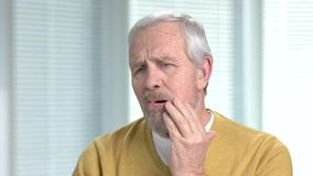 Elderly man with sick tooth. Mature man touching his cheek as suffering from strong tooth ache. Negative human emotions and expressions stock footage