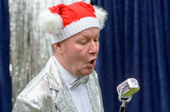 Elderly man singing Christmas songs on stage. Elderly man wearing a festive red Santa hat singing Christmas songs during a stage performance into a microphone in Royalty Free Stock Photos