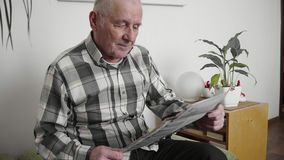 Elderly man sits in a chair and reading a newspaper in a modern apartment 4k. Elderly man sits in a chair and reading a newspaper in a modern apartment stock video footage