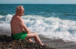 Elderly man sits on seacoast Royalty Free Stock Photos