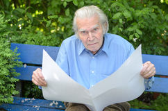 Elderly man sitting alone on a bench in the park Stock Photo