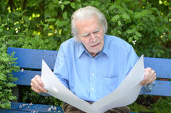 Elderly man sitting alone on a bench in the park Stock Photos