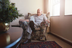 Elderly man sitting on arm chair at old age home Stock Photography