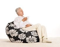 Elderly man sitting in armchair Royalty Free Stock Photography