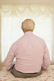 Elderly man sitting on a bed Stock Images