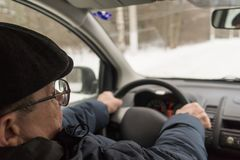 An elderly man is sitting behind the wheel of a car, traveling,. Active way of life Stock Photography