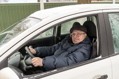 An elderly man is sitting behind the wheel of a car, traveling,. Active way of life Stock Photos