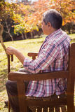 Elderly man sitting on bench with his cane Royalty Free Stock Photo