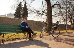 Elderly man sitting on a bench near his bicycle in a city park Stock Image