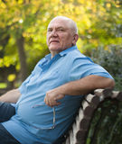 Elderly man sitting on   bench Stock Photo