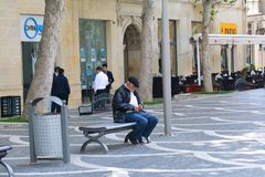 Elderly man sitting on a bench on street Stock Photography