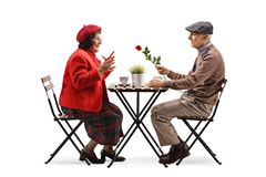 Elderly man sitting at a cafe and giving a red rose to an elderly lady royalty free stock photo