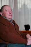 Elderly man sitting in chair Stock Images
