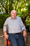 Elderly man sitting in a chair in his garden and looks very frie Stock Photos