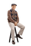 Elderly man sitting on a chair Royalty Free Stock Images