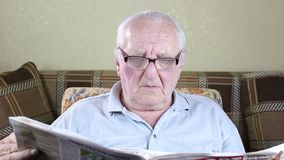 Elderly man sitting in a chair and reading a newspaper. With glasses stock video footage