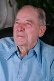 Elderly man sitting in chair , thinking stock photos