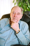 Elderly man sitting in chair , thinking royalty free stock images