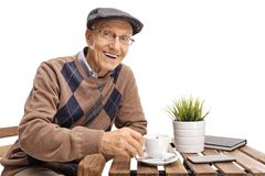 Elderly man sitting at a coffee table and smiling royalty free stock photography