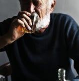 Elderly man sitting drinking whiskey alcoholic addiction bad habit Royalty Free Stock Images