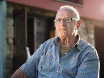 Elderly man sitting in front his house at dawn Stock Photos
