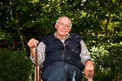 Elderly man sitting in the garden Royalty Free Stock Images