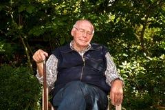 Elderly man sitting in the garden Stock Image