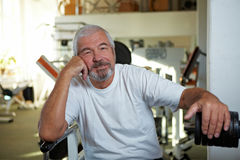 Elderly man sitting in gym Stock Images