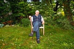 Elderly man sitting happy in his garden Royalty Free Stock Photos