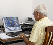 Elderly Man Sitting at his Computer. Stock Photo