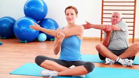 Elderly man sitting in lotus pose stretching arms with his trainer stock footage