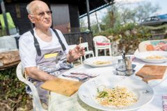 Elderly man sitting at lunch table outdoor. Stock Photography