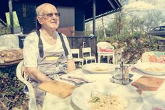Elderly man sitting at lunch table outdoor. Royalty Free Stock Photography