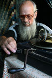 Elderly man sitting next to the old gramophone Stock Photo