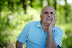 Elderly Man Sitting Outdoors Smiling At The Camera Royalty Free Stock Image