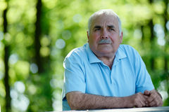 Elderly man sitting outdoors smiling at the camera Stock Photography