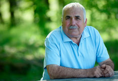 Elderly man sitting outdoors smiling at the camera Stock Photo