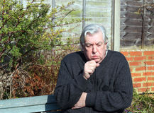 Man with a cold and coughing. An elderly man sitting outside coughing with a bad cold Royalty Free Stock Photography