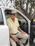 Elderly Man Sitting in Pickup Truck. An elderly man sitting on the seat of a pickup truck with the door open looks out with a concerned look on his face Royalty Free Stock Images