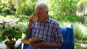 An elderly man sitting and reading a book and drinking juice stock footage
